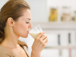 Young Woman Drinking Milk In Kitchen