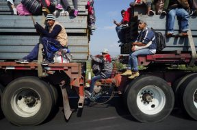 Migrants, part of a caravan of thousands traveling from Central America en route to the United States, travel on top of a truck as they make their way to Irapuato from Queretaro